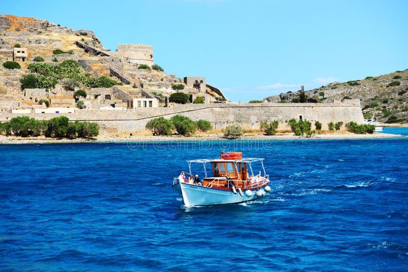 Los yates del motor con los turistas están cerca de isla de Spinalonga fotos de archivo