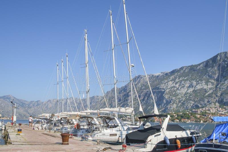 Los yates y los barcos de motor se amarran en el embarcadero en la costa imagen de archivo libre de regalías