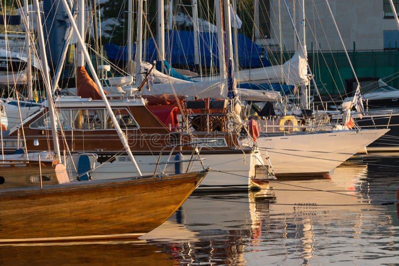 Los yates y los barcos de placer parquearon con el ancla en el puerto fotos de archivo