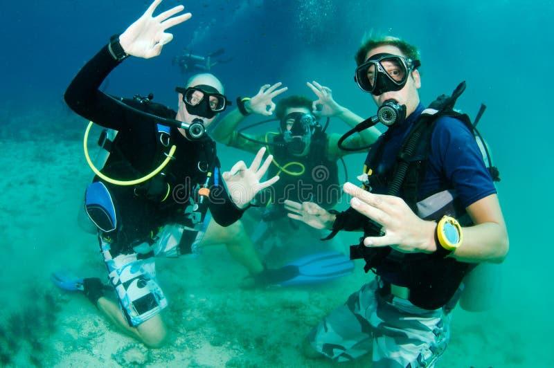 Los zambullidores de equipo de submarinismo aprenden la zambullida gruesa y son felices imagen de archivo libre de regalías
