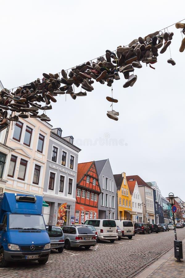 Los zapatos cuelgan en el alambre eléctrico sobre el camino urbano fotos de archivo