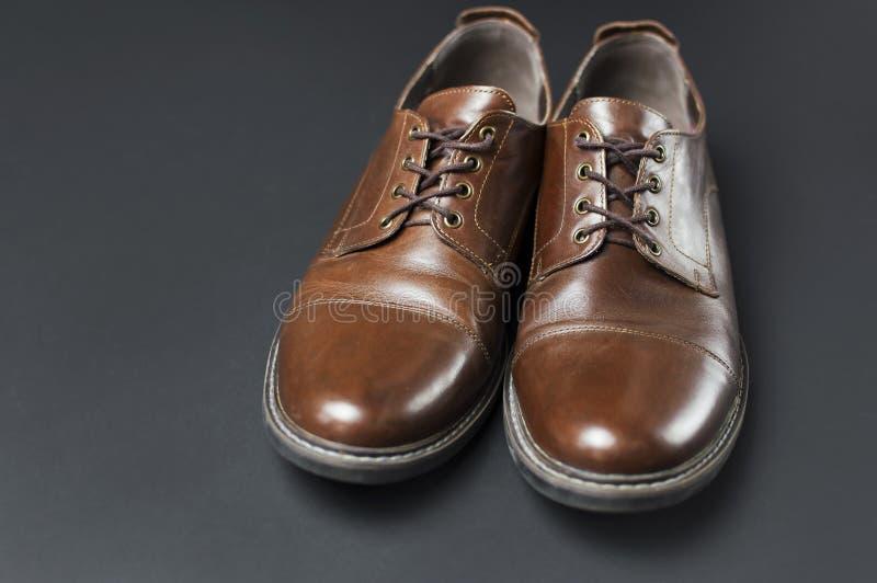 Los zapatos de los hombres de cuero marrones clásicos en endecha negra gris del plano de la opinión superior del fondo con el esp fotos de archivo