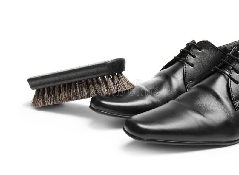 Los zapatos de los hombres elegantes y escobilla en el fondo blanco imagen de archivo libre de regalías