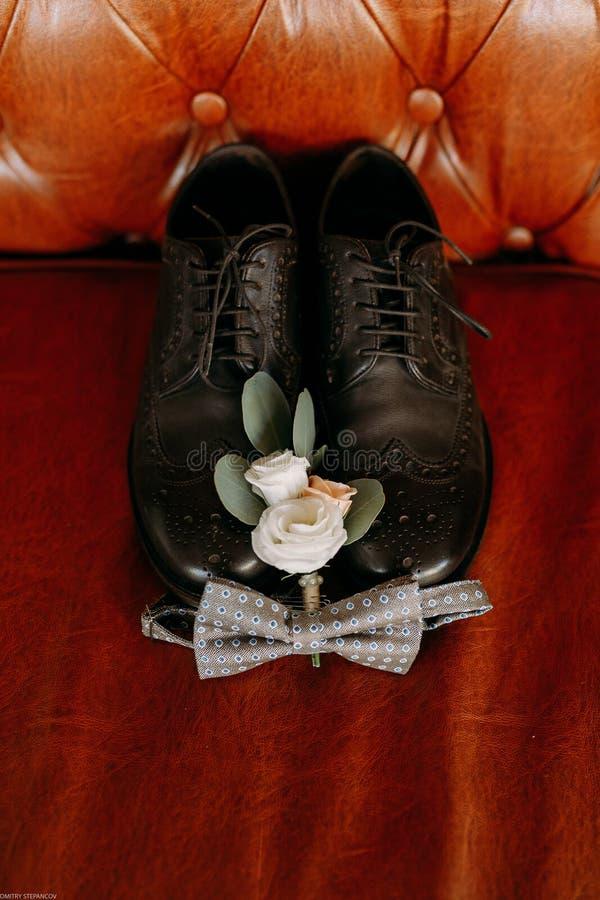 Los zapatos de la boda del negro del ` s de los hombres están situados en el sofá de cuero imágenes de archivo libres de regalías