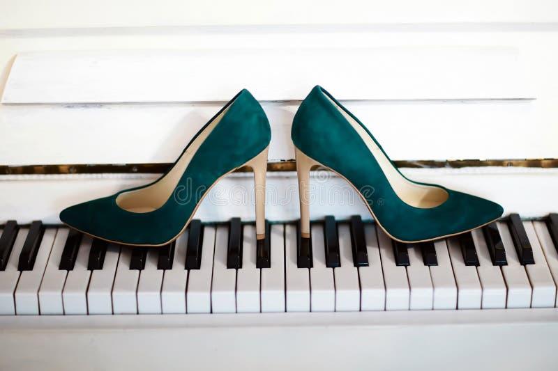 Los zapatos de la novia de tacón alto están en las llaves del piano, blancos y negros, zapatos verdes del terciopelo de las mujer fotografía de archivo