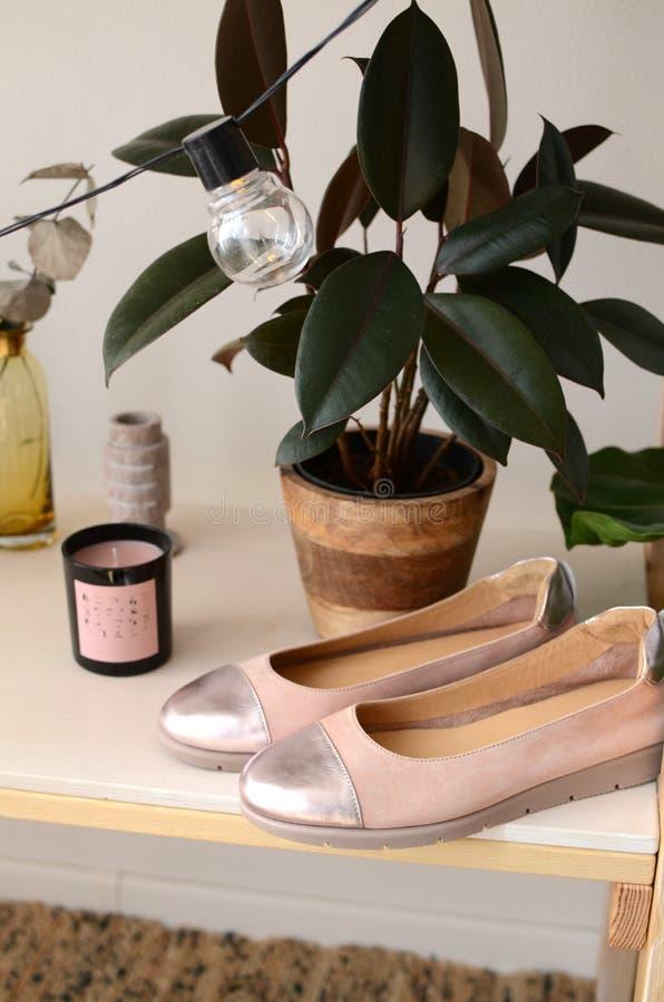 Los zapatos de las mujeres de cuero elegantes de los zapatos beige en los zapatos brillantes ligeros de un fondo de madera con lo fotos de archivo libres de regalías