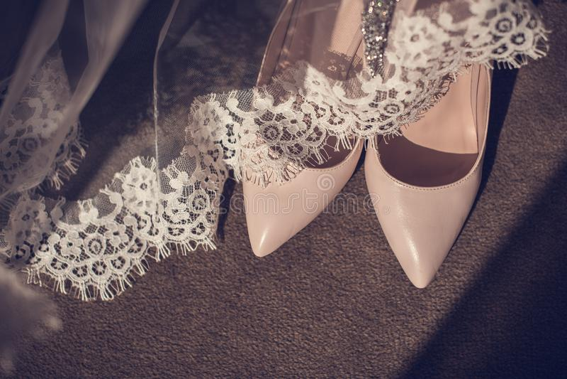 Los zapatos de las mujeres de cuero elegantes de los zapatos en zapatos brillantes ligeros del fondo de madera del talón de una  fotos de archivo