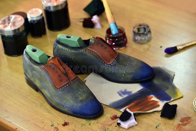 Los zapatos de lujo coloridos hechos a mano del hombre son pintados a mano en una fábrica de la producción fotos de archivo libres de regalías