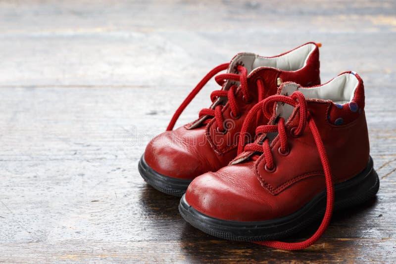 Los zapatos de los niños en un fondo de madera imágenes de archivo libres de regalías