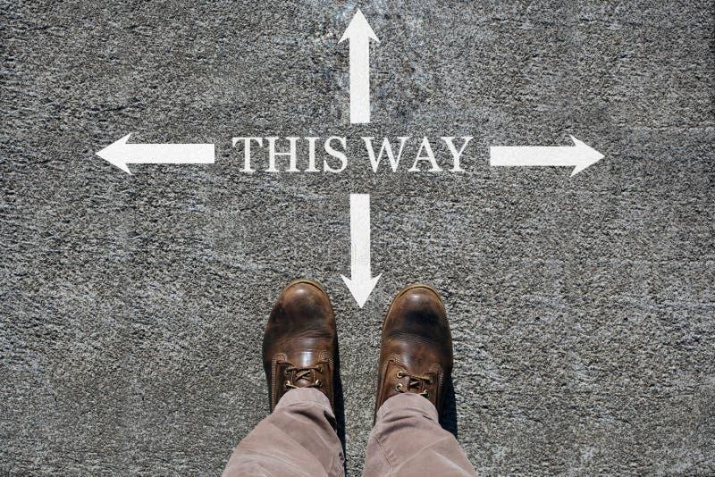 Los zapatos del hombre ven desde arriba, palabras esta manera y una flecha que indica las direcciones con el espacio de la copia  foto de archivo libre de regalías