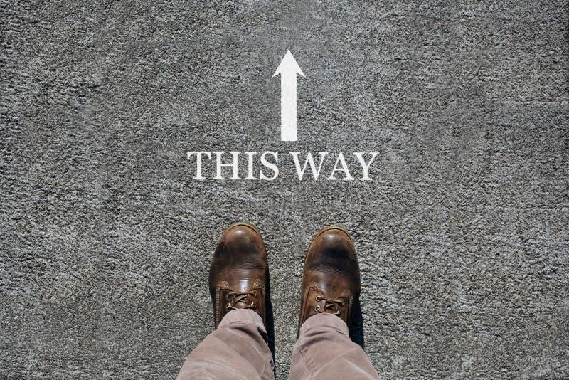 Los zapatos del hombre ven desde arriba, palabras esta manera y una flecha que indica las direcciones con el espacio de la copia  foto de archivo