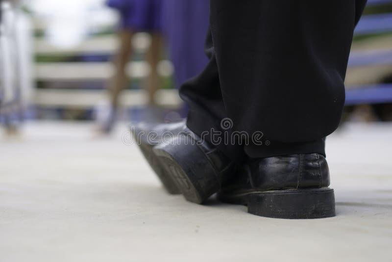 Los zapatos negros del árbitro de encajonamiento en el ring de boxeo Foco suave imagenes de archivo