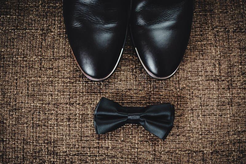 Los zapatos negros y la mariposa negra mienten en el despido marrón fotografía de archivo libre de regalías