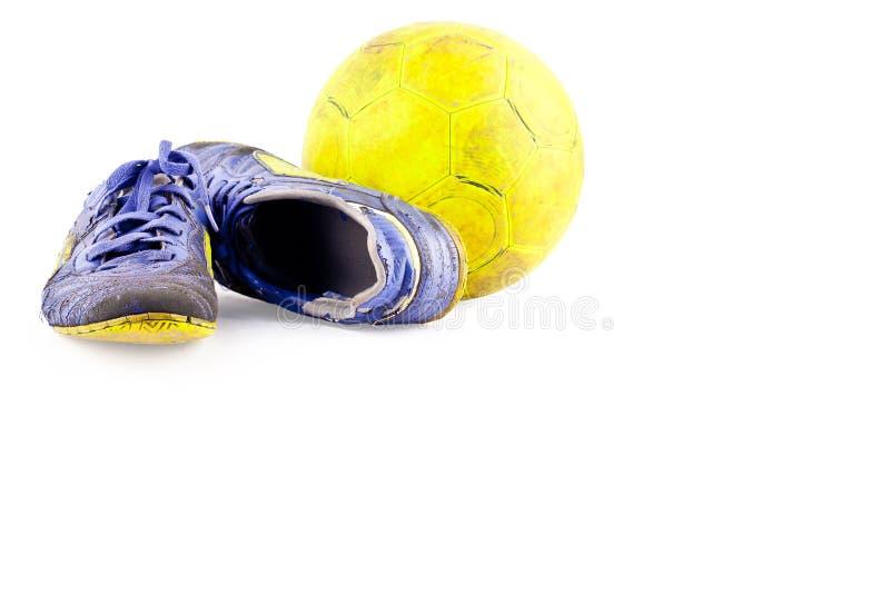 Los zapatos viejos del fútbol dañaron y bola futsal amarilla sucia vieja en el objeto blanco del fútbol del fondo aislado imagen de archivo