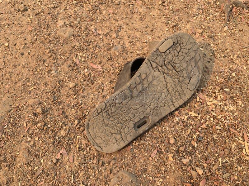 Los zapatos viejos en el piso de la arena fueron dañados Los lenguados de los zapatos fueron llevados caminando durante mucho tie fotografía de archivo