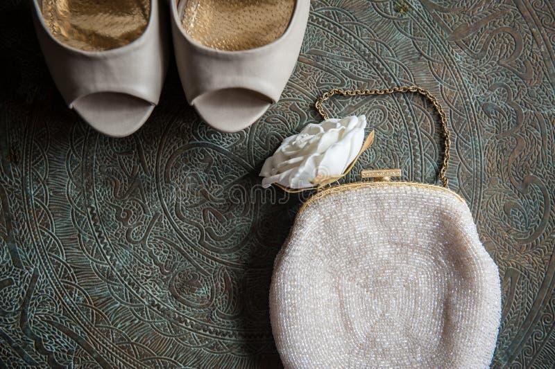 Los zapatos y el embrague de las mujeres de la boda en la bandeja de cobre amarillo con un ornamento fotos de archivo