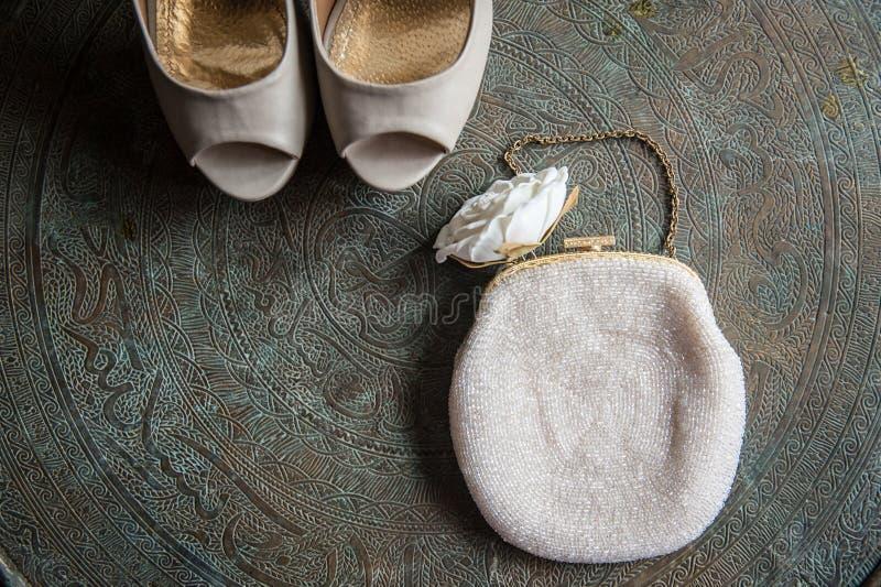 Los zapatos y el embrague de las mujeres de la boda en la bandeja de cobre amarillo con un ornamento foto de archivo libre de regalías