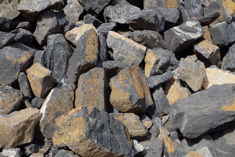 Losas de piedra apiladas en un stonepit - rocas con forma, amarillo y gris planos irregulares coloreadas, machacado en una mina imagen de archivo libre de regalías