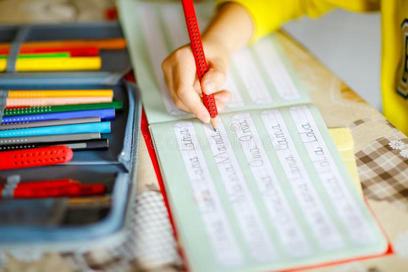 Lose-up of little kid boy at home making homework, child writing first letters and words like mama with colorful pens. Elementary school and education stock photos