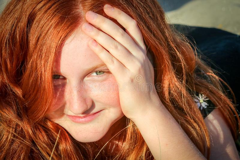 Lose up of Red haired girl with sand on her face at New Zealand beach stock images