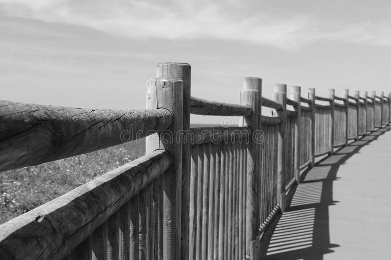Lose up on wooden fence on the walkway on atlantic coast in black and white, saint jean de luz, basque country, france stock photography
