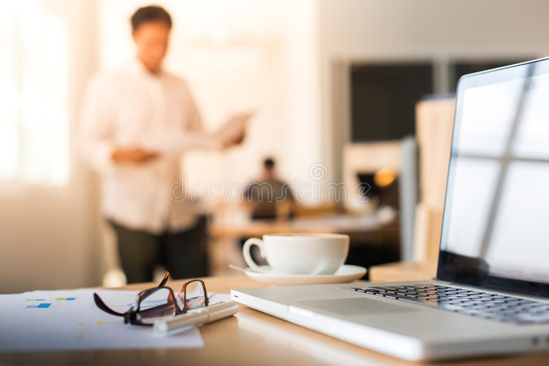 lose-up of workplace in modern office with business people behind and morning light and vintage tone royalty free stock images