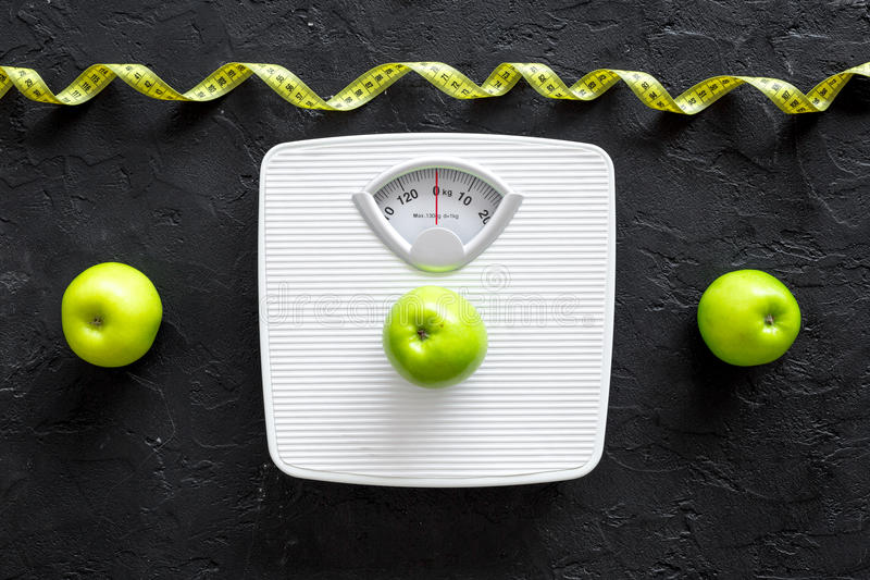 Lose weight concept. Bathroom scale, measuring tape, apples on black background top view stock images