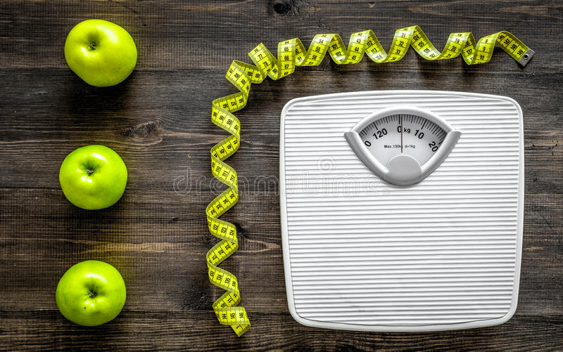 Lose weight concept. Bathroom scale, measuring tape, apples on wooden background top view royalty free stock photography