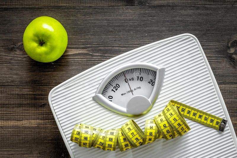 Lose weight concept. Bathroom scale, measuring tape, apples on wooden background top view royalty free stock image