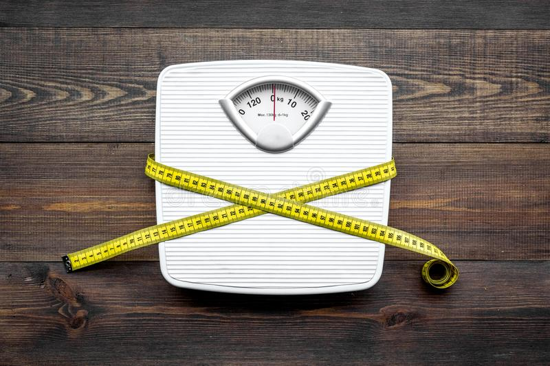 Lose weight concept. Scale and measuring tape on dark wooden background top view royalty free stock photos
