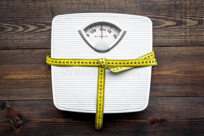 Lose weight concept. Scale and measuring tape on dark wooden background top view stock images