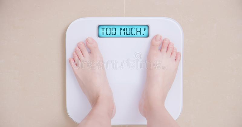 Lose weight concept with scale. Lose weight concept with woman on a scale shows too much stock photos