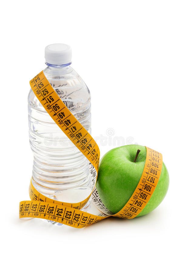Lose weight. Green apple, bottle of water and tape measure royalty free stock photos