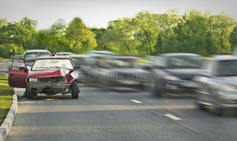 Loser. Crashed old car among traffic flow stock photo