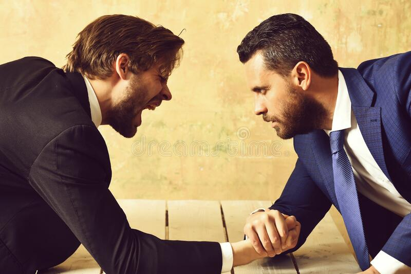 Loser man shouting, arm wrestling defeat and victory of businessman. In suit stock photography