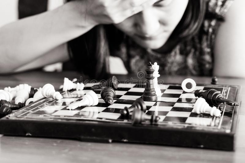 The loser women sad after fighting the chess, committed, competition, winner, successful, dedicate concept - B&W filter applied. The loser woman sad after stock image