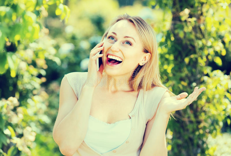 Loseup  Ñ усмехаясь молодой женщины говоря на мобильном телефоне outdoors стоковое фото rf