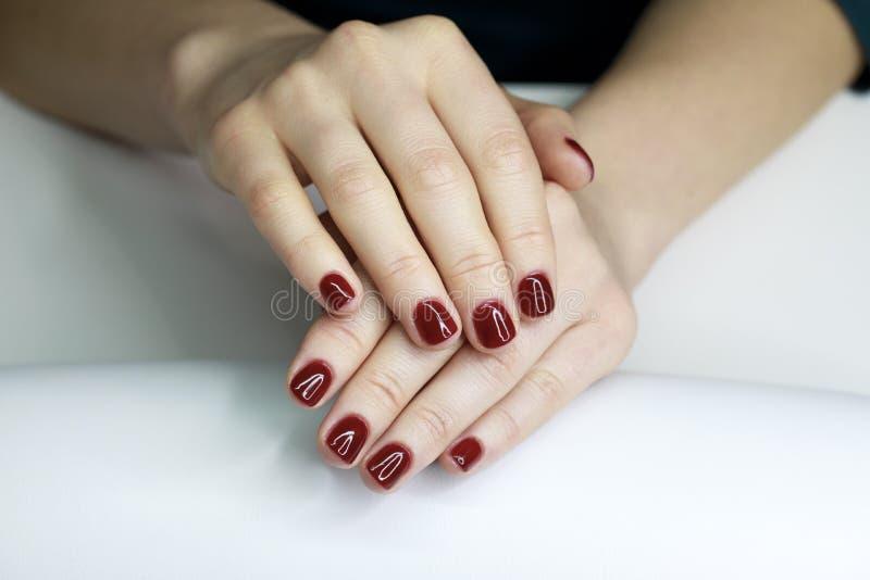 Loseup de ¡ de Ð des mains d'une jeune femme avec la longue manucure rouge sur le NaI image stock