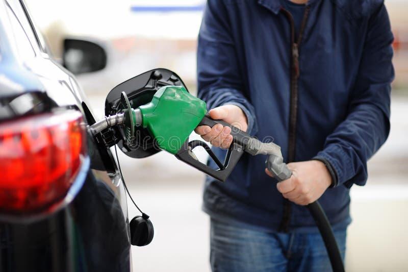 ? loseup del combustibile di pompaggio della benzina dell'uomo in automobile alla stazione di servizio fotografia stock libera da diritti