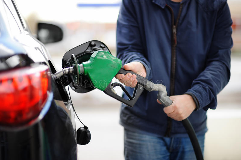 ?loseup of man pumping gasoline fuel in car at gas station royalty free stock photo