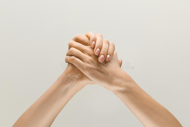 Loseup shot of human holding hands isolated on grey studio background. Win together. loseup shot of male and female holding hands isolated on grey studio stock photos