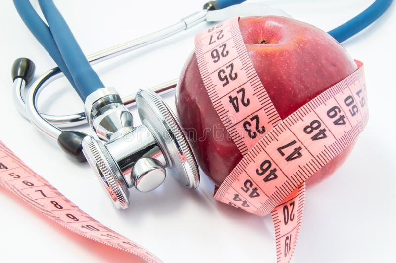 Losing weight with healthy food fruits and vegetables under doctor supervision. Red apple wrapped up by measuring tape and steth stock image