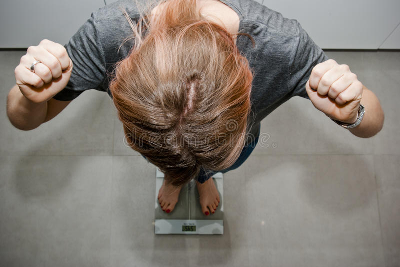 Losing weight. Young woman standing on kitchen scales expressing her joy on losing some weight
