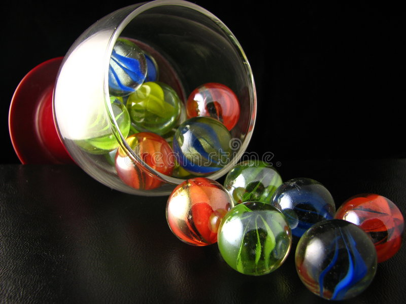 Losing your marbles. This is a shot of my marble collection streaming out of a brandy glass stock photos