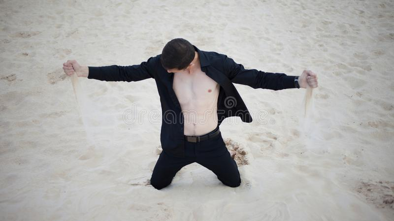 Loss, concept. young man kneeling in the desert. Sand through fingers royalty free stock images
