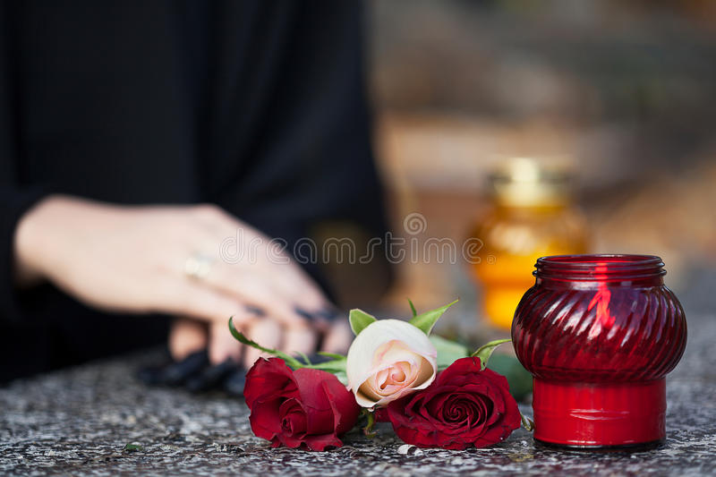 Loss of relative. Woman in mourning arranging flowers and candles on the gravestone stock photo