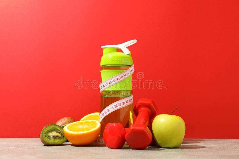Loss weight accessories on grey table. Against red background royalty free stock photos