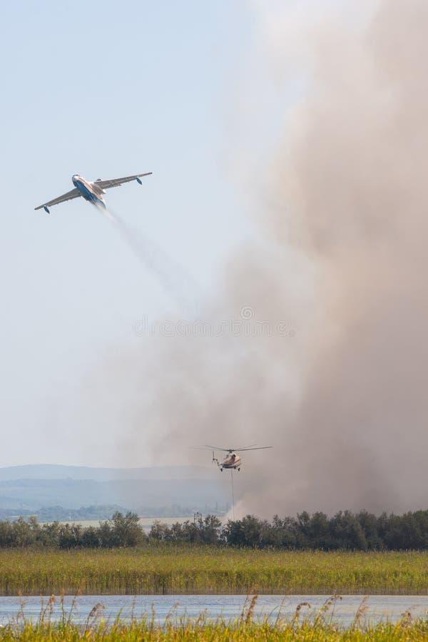 Lossing van water bij het branden van riet door vliegtuig en helikopter, op een brand op de alluviale gebieden van de Anapka-Rivi stock afbeelding