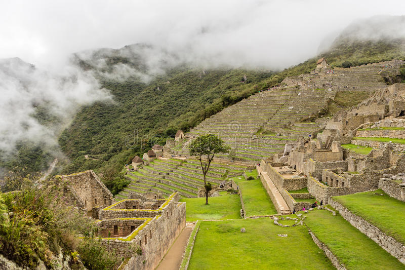 Lost ancient Inca city. Of Machu Picchu with green lawns in rainy and foggy weather stock photos