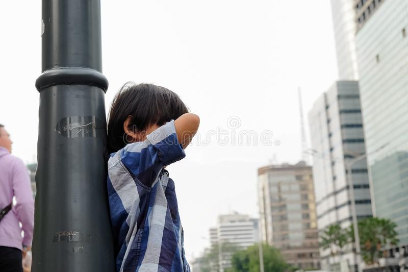 Lost Asian Child Seems Crying Lean Back His Body to a City Lamp Pole stock images